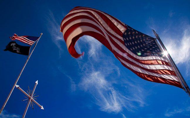 U. S. flags flutter in a steady breeze under gorgeous skies near Fort Defiance, Arizona.