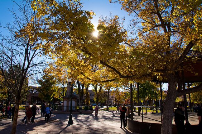 Brilliant sunshine spills through autumn-tinged trees into The Plaza at Santa Fe.