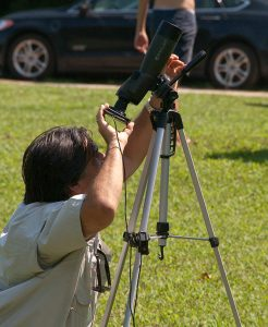 A man uses a telescope linked to his smart phone to view the solar eclipse.