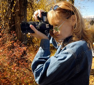 My wife Abby makes pictures of cottonwood trees in southern Colorado, October 2005, with her Nikon D70S; note that she is correctly holding her camera