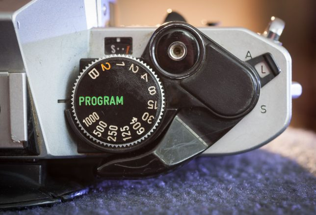 "The shutter speed dial can be set to program which, in combination with setting the aperture ring on the lens to ""A"" will allow the camera to set both shutter speed and aperture."