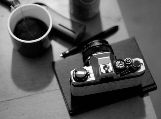 A camera and a cup of tea sit on a table.