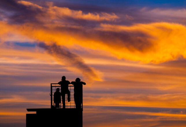 Coaches are silhouetted against a beautiful late-summer sky at a football game in Stratford, Oklahoma.
