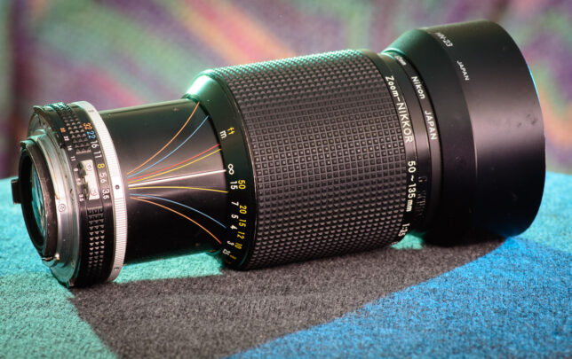 "My ""new"" 30-something Nikkor 50-135mm f/3.5 sits in my studio. I had never seen one in the field, so I think it's safe to say it was an undiscovered asset. The outward-swooping colored lines are the depth of field scale, which changes with focal length."