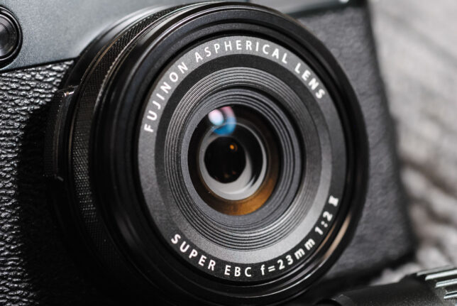 The lens on the Fujifilm X100V is a fixed (non-interchangeable) 23mm f/2.0.