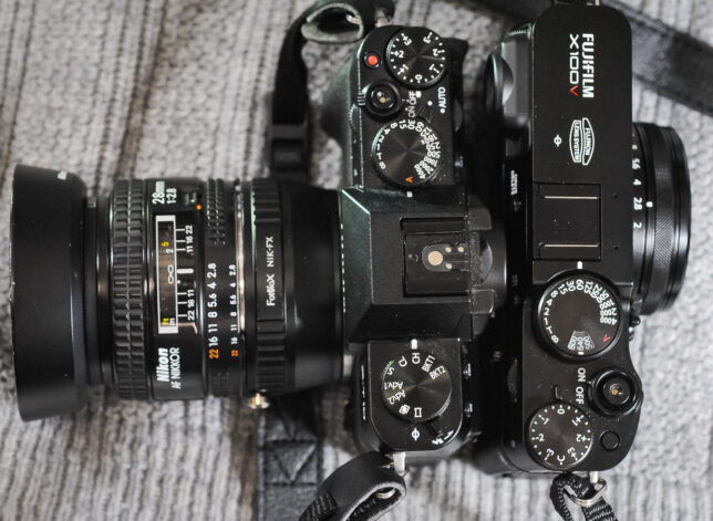 I placed my Fujifilm X-T10 mirrorless camera back-to-back with the Fujifilm X100V. As you can see, the camera body of the X-T10 is smaller, but after adding an lens adapter and a lens in the same class as the 23mm on the X100V, the two cameras are laid out quite differently.
