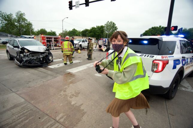 Mackenzee Crosby scampers like a roadrunner across the street last week at the scene of a crash at Main and Oak. In her hands is her new Fujifilm X100V.