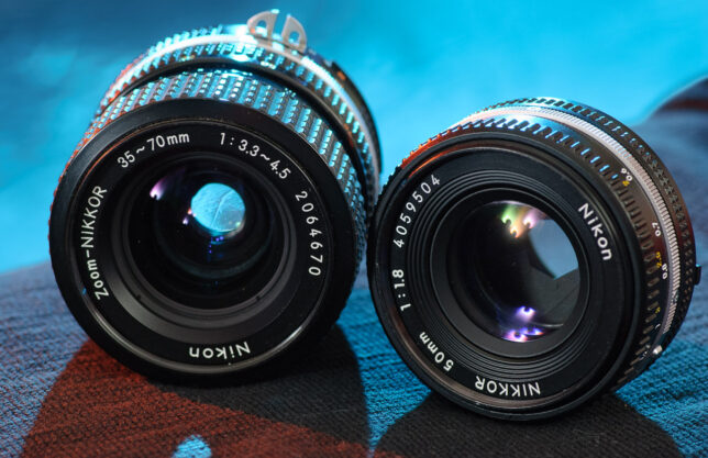 The Nikkor 35-70mm f/3.3-4.5 and the Nikkor 50mm f/1.8 sit face-to-face. These lenses were regarded as affordable in their day, but are built to mechanical standards almost unheard of in 2021.