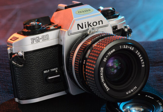 """The Nikon FG-20 is shown with a Nikkor 35-70mm f/3.3-4.5 """"kit lens"""" mounted on it."""