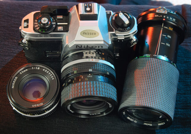 The Nikon FG-20 is shown with the 50mm f/1.8 Nikkor, the 35-70mm f/3.3-4.5 Nikkor, and the Vivitar 70-210mm f/4.5.
