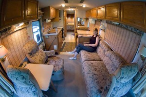 """Abby sits on the couch in the main """"living room"""" area of the RV; this couch folds down to make a bed, as does the dining table; in the back is a queen-size bed."""
