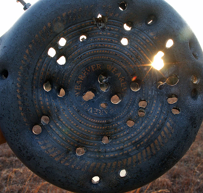 Sun shines through bullet holes in an aluminum saucepan we use for target practice down at the pond.