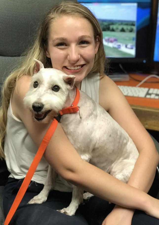 Ashlynd holds her dog, Jack Frost Huffman, at her desk in the newsroom.
