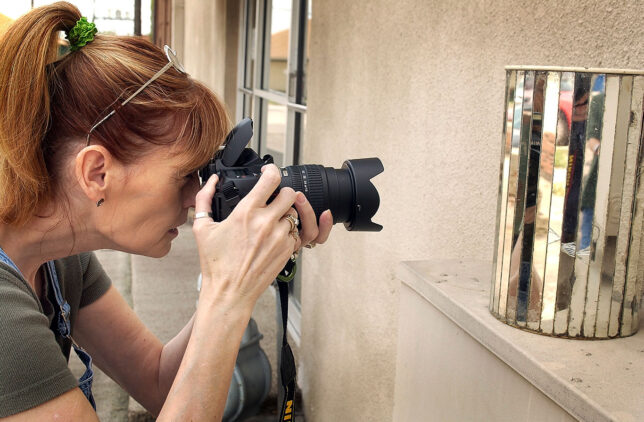A beautiful woman with a camera in her beautiful hands with a pony tail? So very.