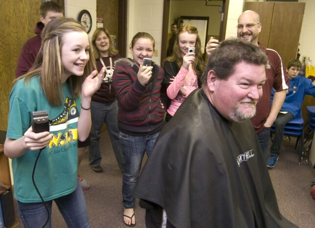 Mackenzee Crosby shaves the head of Ada Junior High science teacher Luke Penrod Thursday, March 8, 2012, as a reward for collectively giving over 100 units of blood products at the recent AJH blood drive. Assisting the seventh graders was beautician Kourtnie Rhodes.