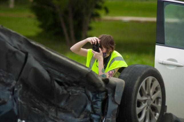 Mackenzee makes pictures at the scene of a car crash near Ada High School in June.