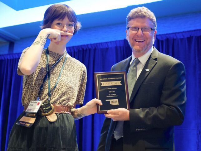 """Mackenzee accepted an award for Sports Editor Jeff Cali at the Oklahoma Press Association's annual convention in June, do the """"finger 'stache"""" gesture."""