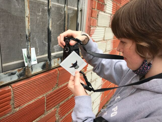 """Mackenzee Crosby photographs some of her Polaroid images in a windowsill in an alley as she and I were on a """"photo walk"""" on a rainy day in May."""