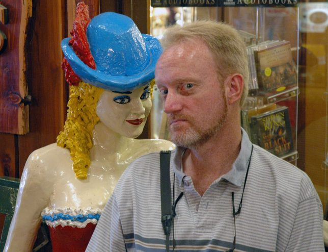 The author poses with a life-size statue of a burlesque performer at Wall Drug.