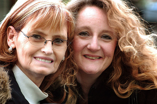 Abby and Nicole smile for a portrait outside Nicole's house.