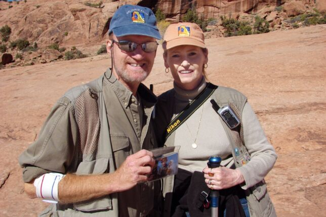 Abby and I pose for a photo on the Delicate Arch trail. I am holding a photo of us getting married at Delicate Arch in 2004.