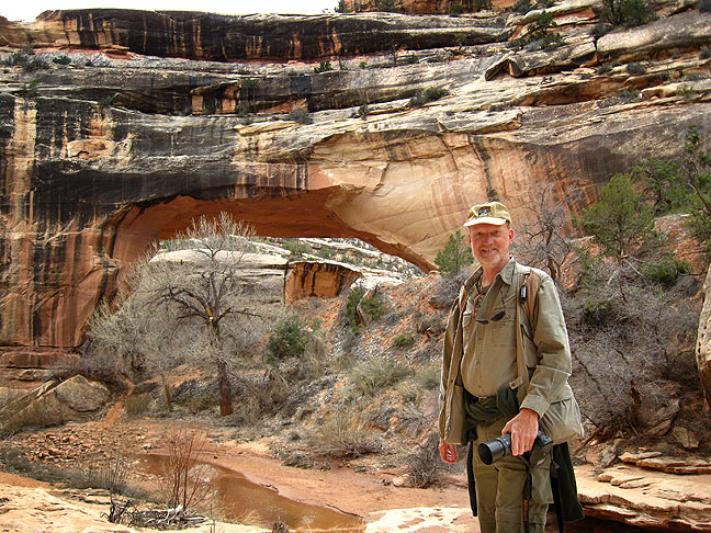 THe author poses at Kachina Bridge after hiking much of the White Canyon trail; note my fleece tied around my waist, since it was cold in the morning but warmer when I returned.