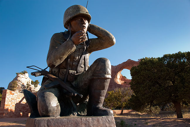 """This bronze memorial to the legendary Navajo """"Code Talkers"""" at Window Rock, Arizona stands about 12 feet tall, with the Window Rock itself, a large natural arch, in the background."""