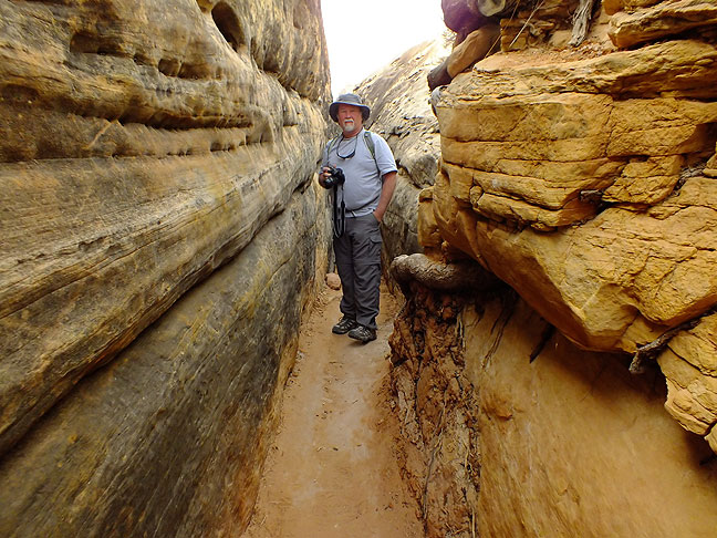 """Jim poses in the entrance to """"the crack"""" on the Chesler Park trail at Canyonlands."""