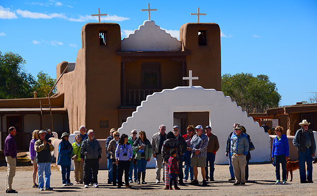A tour group huddles around their guide outside the church at Taos Pueblo. Photography is not permitted inside the church, but exterior shots are perfectly fine.