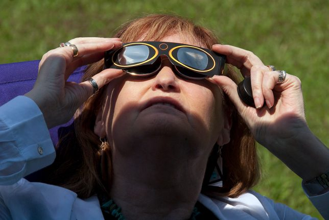 Abby uses her eclipse glasses to watch the crescent sun as the totality approaches.