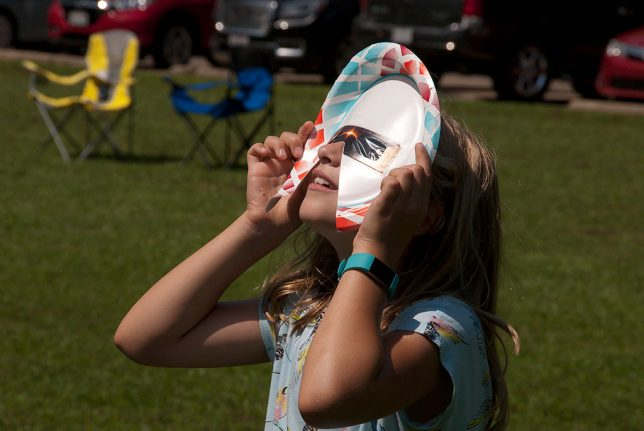A young girl looks at the sun with eclipse glasses added to a paper plate for extra protection from the sun.