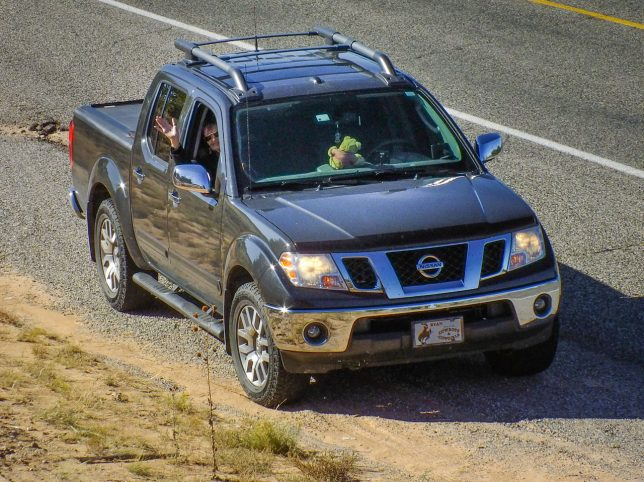 Abby waves at me from the truck after I scampered up a hill to make a picture.