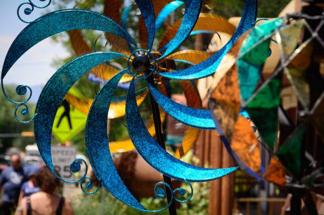 Steel flowers spin in a light breeze as I walked the four blocks from our lodging to The Plaza in Taos.