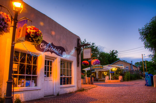 Lights come up in shops on The Plaza as the golden moment becomes the blue hour in Taos.